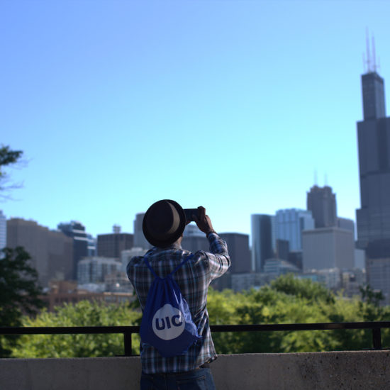 Student taking a picture of Chicago Skyline with phone